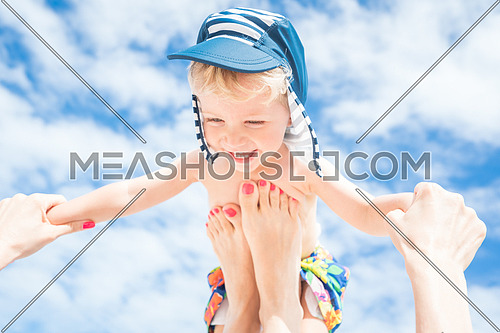 Happy moment,Mother throws up her smiling baby boy in the blue sky,summer time