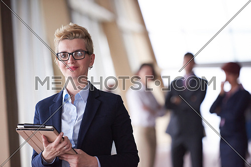 Smilling young business woman with tablet computer  in front her team blured in background. Group of young business people. Modern bright  startup office interior.