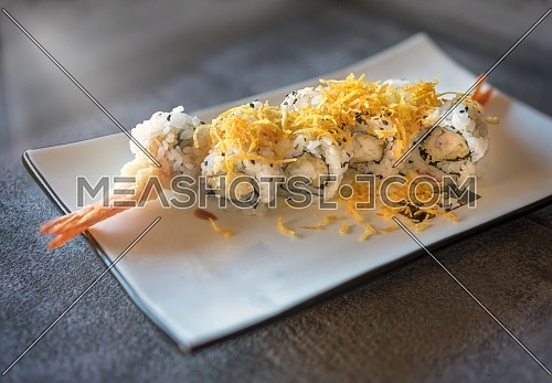 Prawn sushi served on rectangular white plate on dark gray stone background