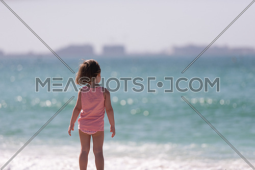 happy little girl at the seaside in the summer.Adorable little girl at beach during summer vacation. Happy baby by the sea or ocean