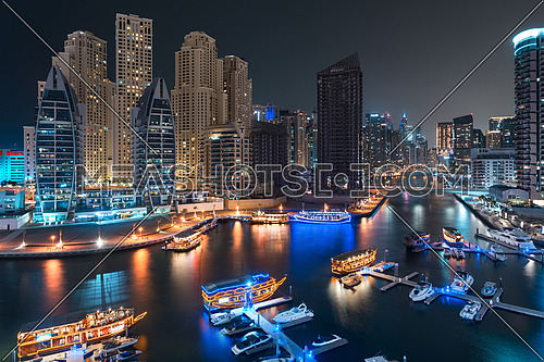 Dubai Marina Bay at night with beautiful towers and yachts reflected on water on water