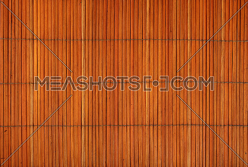 Orange brown vintage natural wooden bamboo mat background texture with vertical planks, close up