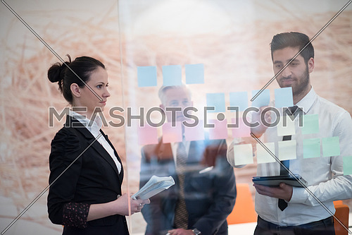 young creative startup business people on meeting with older senior mature businessman at modern office making plans and projects with post stickers on glass
