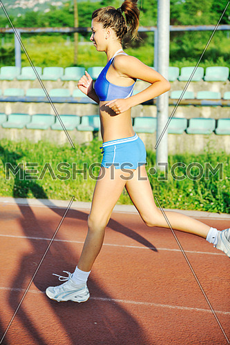 beautiful young woman exercise jogging and runing on athletic track on stadium at sunrise