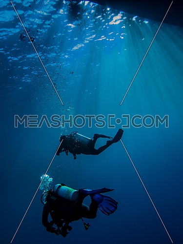 Two divers moving towards their boat