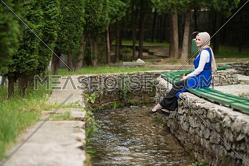 Portrait Of Young Muslim Woman Sitting On A Bench Next To The River