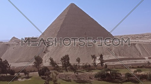 Reveal shot for The Great Pyramid of Khufu from Green field in background in Giza at day