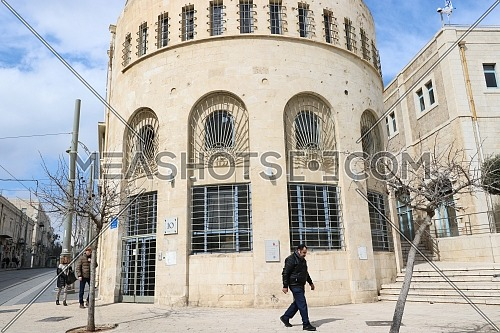 A man walks in front of the Jerusalem Municipality building and shows bullets from the days of the 1948 war