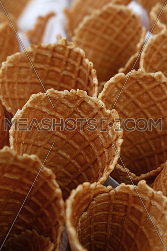 Several empty fresh wafer ice cream cone cornet cups with white paper napkins, close up, elevated high angle view