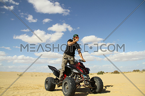 young middle eastern quad motorcycle driver enjoys driving around the desert on a sunny day