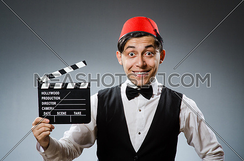 Man with movie board wearing fez hat