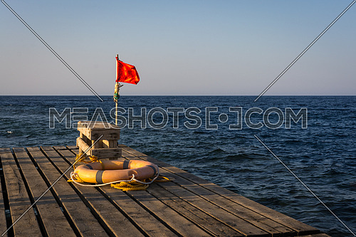 Red flag for warning and lifebelt on a  old wooden pier for diving and snorkeling at sunset.copy space.