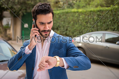 A young man is talking in the mobile phone in the street and he is angry