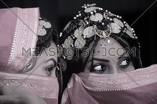 two girls wearing a traditional dress partially covering their face