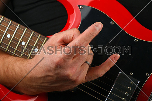 Male hand holding red sg guitar body under neck with devil horns rock metal sign isolated on black background