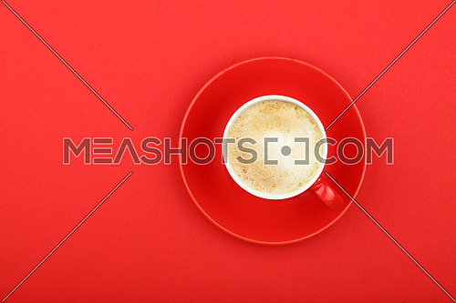 One full morning latte cappuccino or macchiato coffee with milk froth in small red cup with saucer on red paper background, top view, bird eye view
