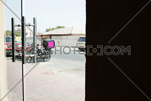 A delivery motorcycle parked infront of a restaurant