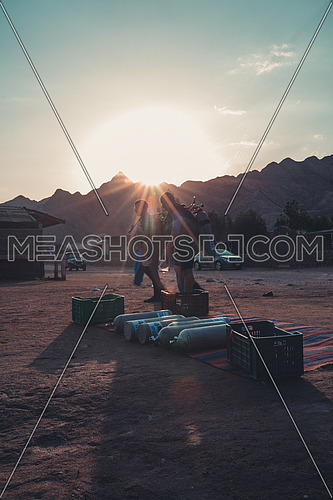 Two divers passing by the diving gear placed on shore next to a mountain at sunset in Dahab