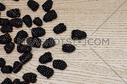 Blackberries settled on a wooden background