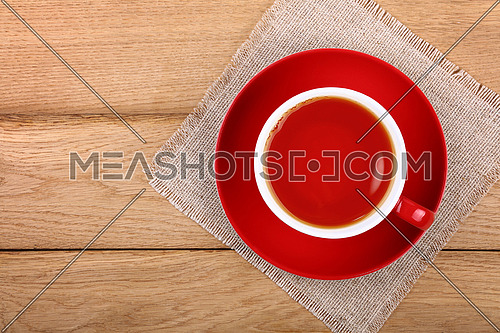 Full cup of black tea on red porcelain saucer over wooden table with textile tablecloth napkin, close up, elevated top view, directly above