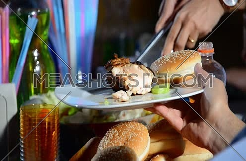 Close up shot for female hand sharing salad into plate