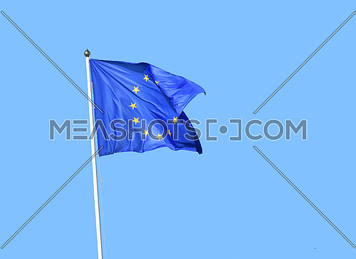 European Union EU flag flying in the wind over clear blue sky, side view