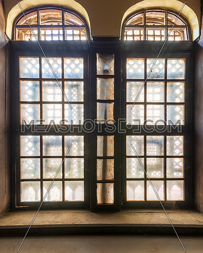 Large grunge vintage window with ornament located inside empty room
