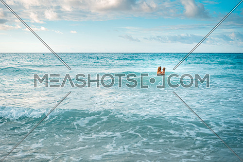 mother and son alone in the turquoise ocean,mom hugs her son,copy space.