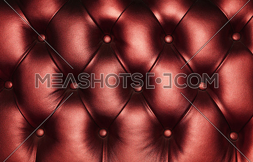 Burgundy dark red capitone genuine leather background, retro Chesterfield style soft tufted furniture upholstery with deep diamond pattern and buttons, close up