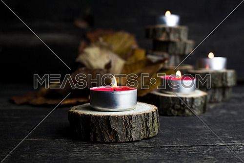 Christmas candles burning, decoration on wooden logs resting on rustic wooden background