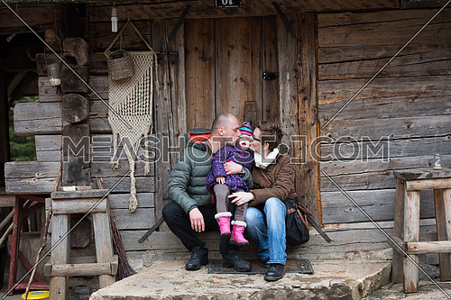 portrait of young family with little child sitting together in front of old retro wooden house