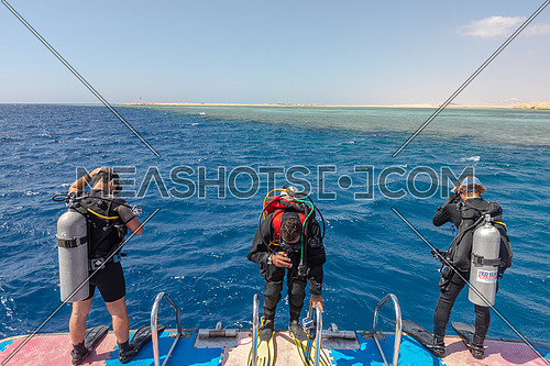 Long shot for divers getting ready to dive into Red Sea from a yacht at day