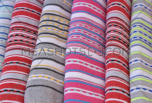 Close up colorful linen textile towels, beach mat coverlets and bedspreads on retail display