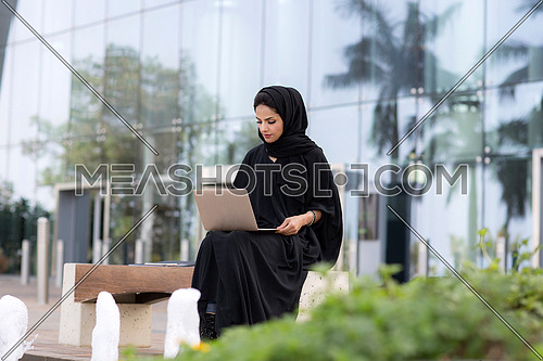 Saudi lady working on her laptop in public