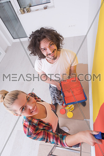 happy smiling young couple painting interior wall of new house