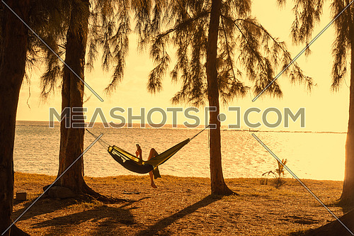 Silhouette of woman reading tablet in hammock,beach vacation in vintage style.