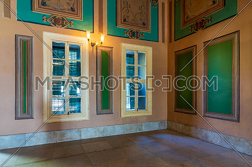 Corner orange wall with two wooden windows with green shutters, beautiful elegant rectangular green frames with ornate border, and white tiled marble floor