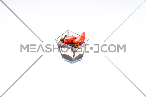 In the picture a cupcake with strawberry,cream and chocolate in a plastic cup,isolated on white background.