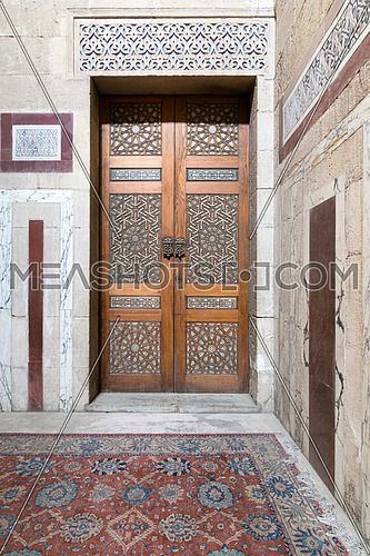 Ancient decorated door (arabesque) and decorated colored marble wall, Medieval Cairo, Egypt