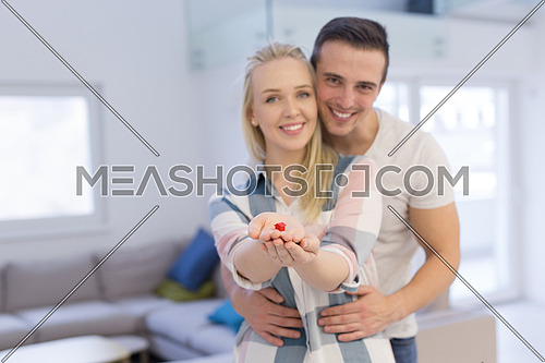 Happy couple hugging and showing small red house in hands Concept of buying house to start a family