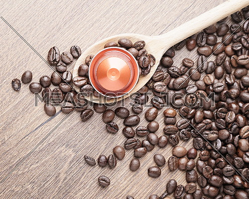 Coffee capsule on wooden spoon and roasted coffee beans on wooden background,top view,close up.