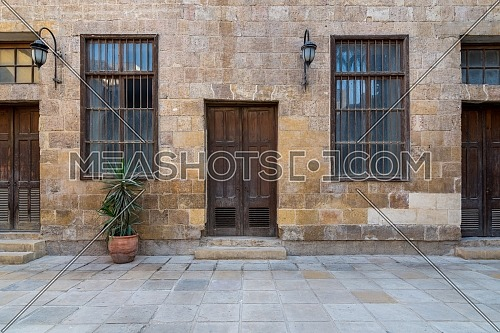 Facade of old abandoned stone bricks wall with wooden doors, windows covered with iron bars and lanterns, Cairo, Egypt
