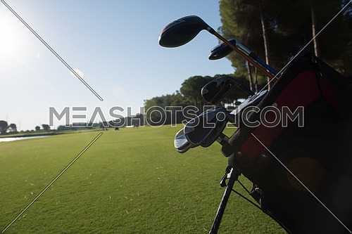 close up of golf bag on course with  club and ball in front at beautiful sunrise