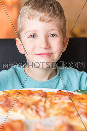 Beautiful happy young boy smiling and eating fresh made pizza,He sit at black chair, He has blonde hair.