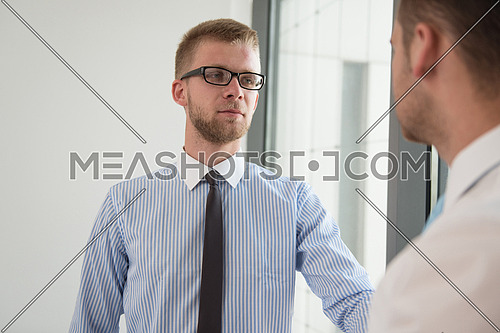 Happy Businessmen Shaking Hands While Standing In Office