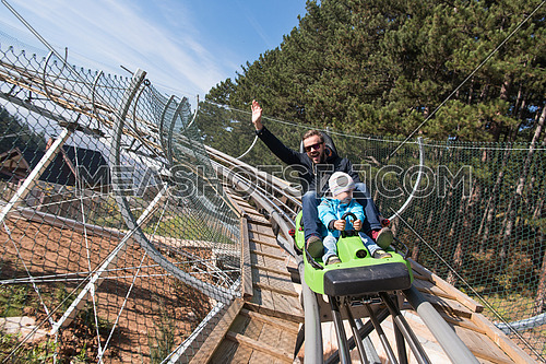 Excited father and son enjoys driving on alpine coaster