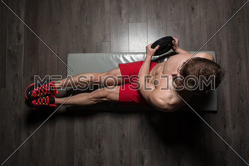 Healthy Young Man Exercising Abdominals On Foor With Weights