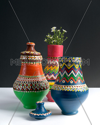 Three decorated pottery vases with small flowers