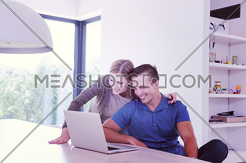 Young couple using laptop computer at luxury home together, looking at screen, smiling.