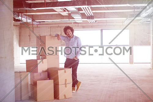 portrait of young businessman on construction site checking documents and business workflow with cardboard boxes around him in new startup office